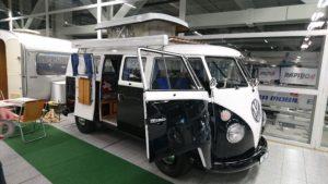 Schwarz-weisser VW Bulli mit geöffneten Türen