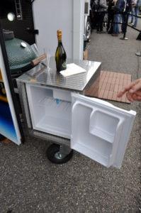 Kühlschrank auf Rollen geöffnet und mit Champagner